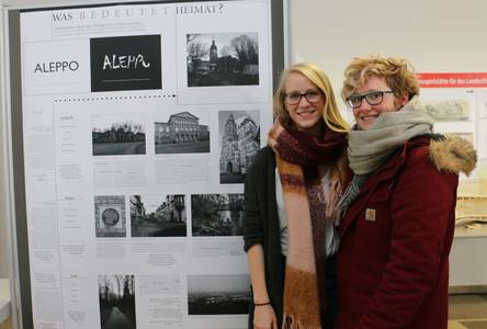 Studierende neben dem Plakat zum Thema Heimat
