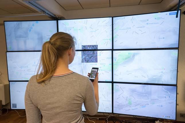 Frau vor einer Wand aus Bildschirmen, die einen Stadtplan darstellen
