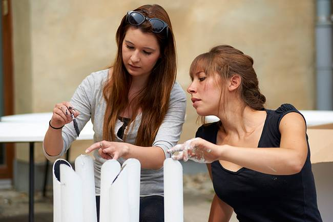 Two young females working on an architect project using their hands and a bursg. One hand covered in white paint.