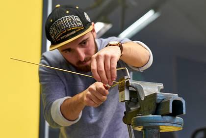 Junger Student der im Stehen mit einer Säge arbeitet