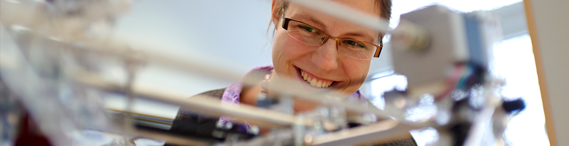 Smiling female looking at an experimental setup in the laboratory